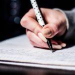 ノートに文字を書いている人の画像