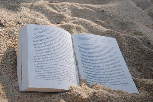 砂の上に置かれている本の画像