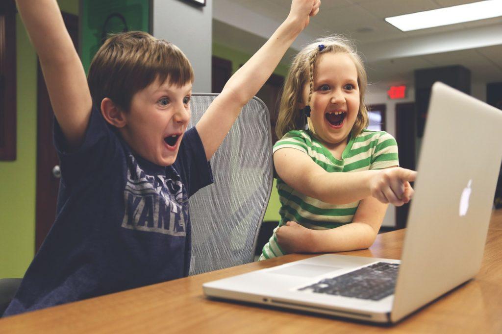 パソコンを見ながら喜ぶ子供たちの画像