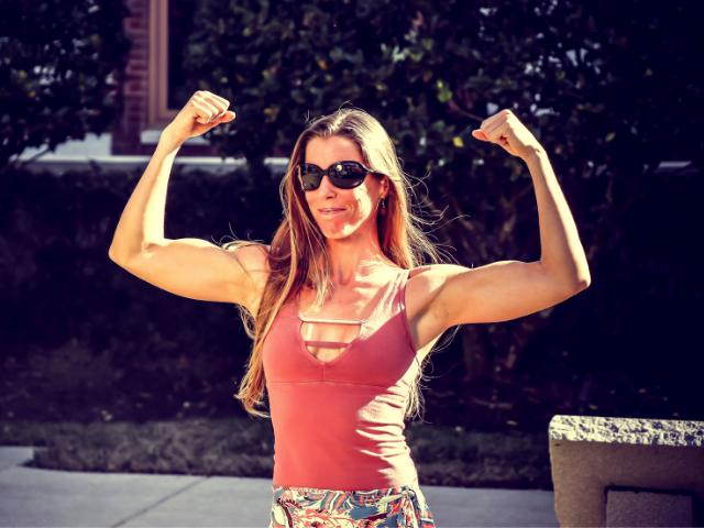 腕の筋肉をアピールする女性の画像