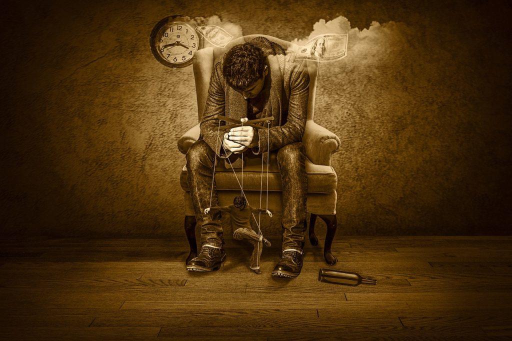 椅子に腰かけてうつむく男性
