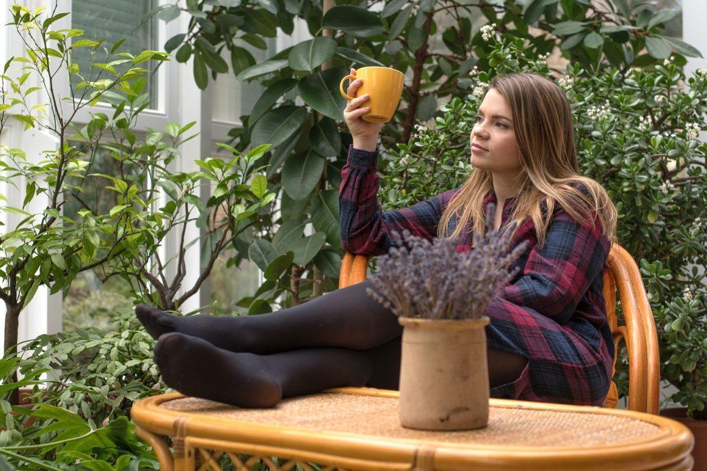 手にカップを持っている女性の画像