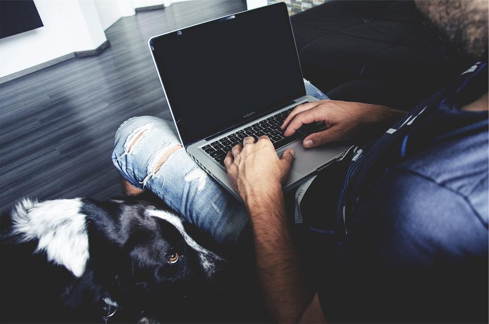 膝の上にノートパソコンを載せている男性の画像